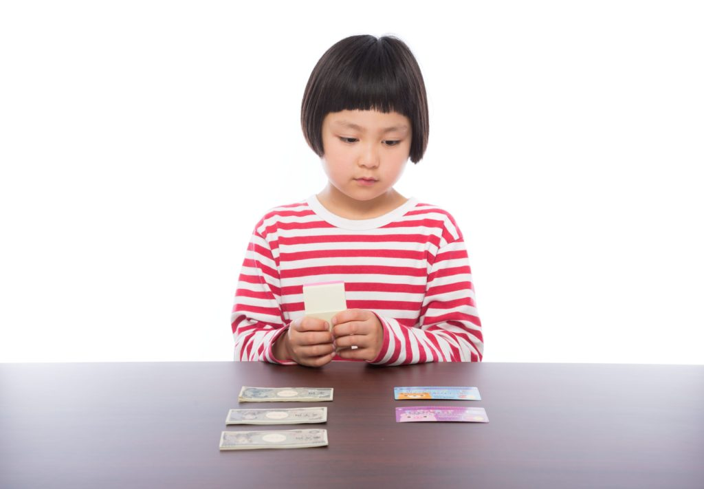 お金を見つめる少女